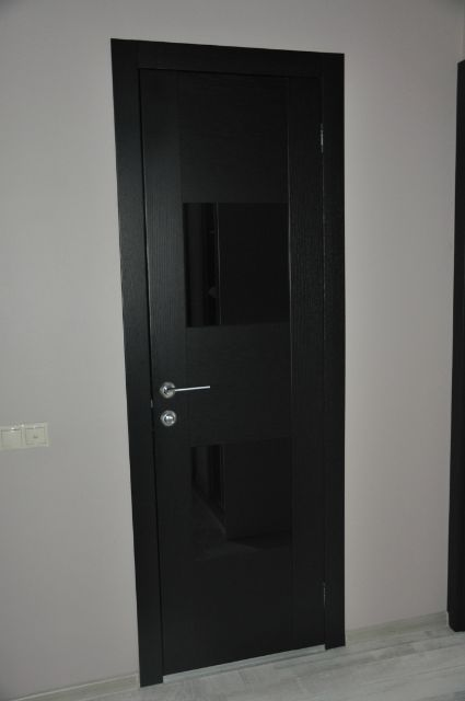 Black door in a bright room