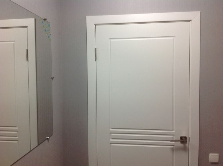 White interior doors – design with gray walls and a large mirror