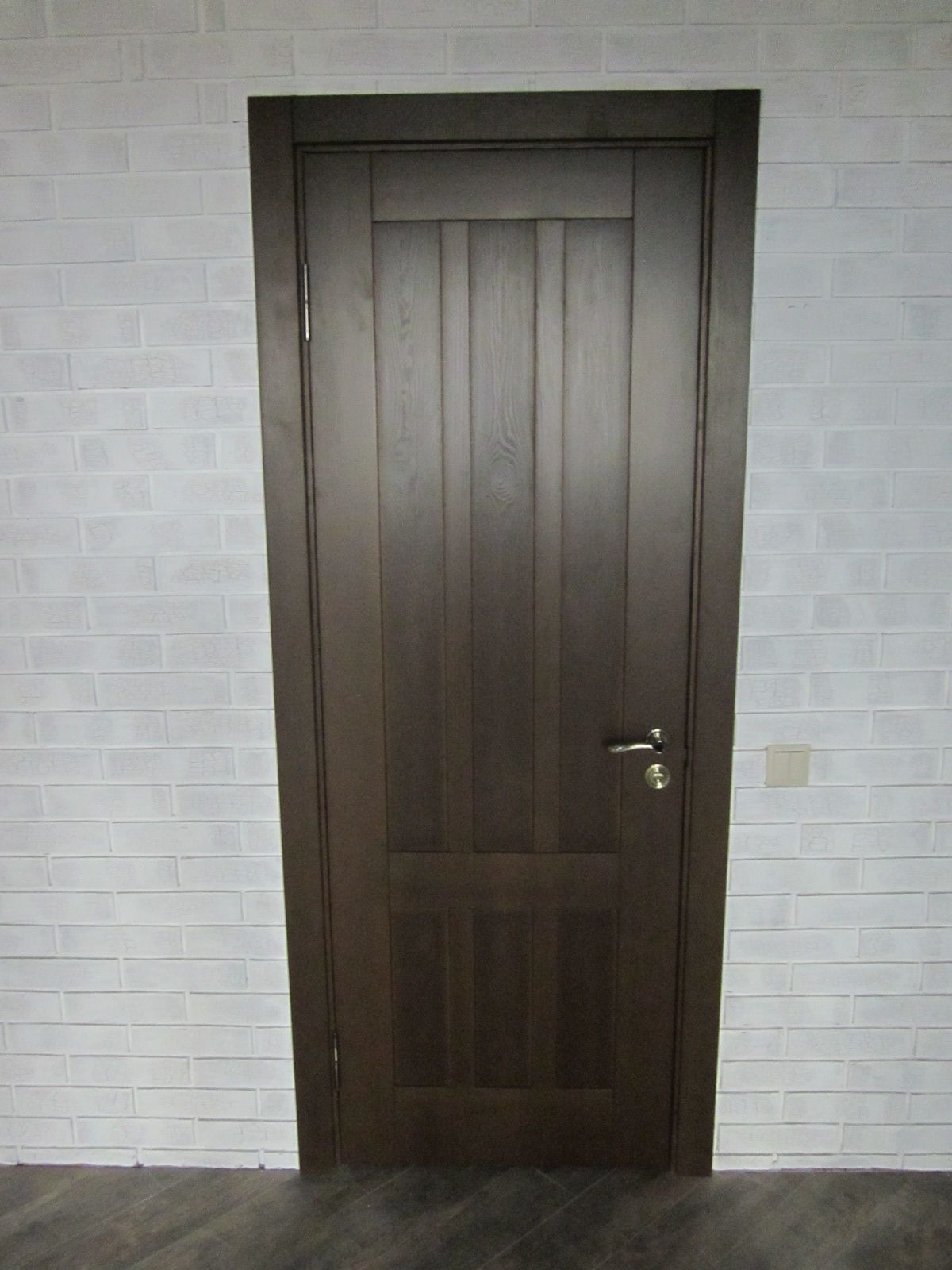 Dark wooden interior door and white brick wall