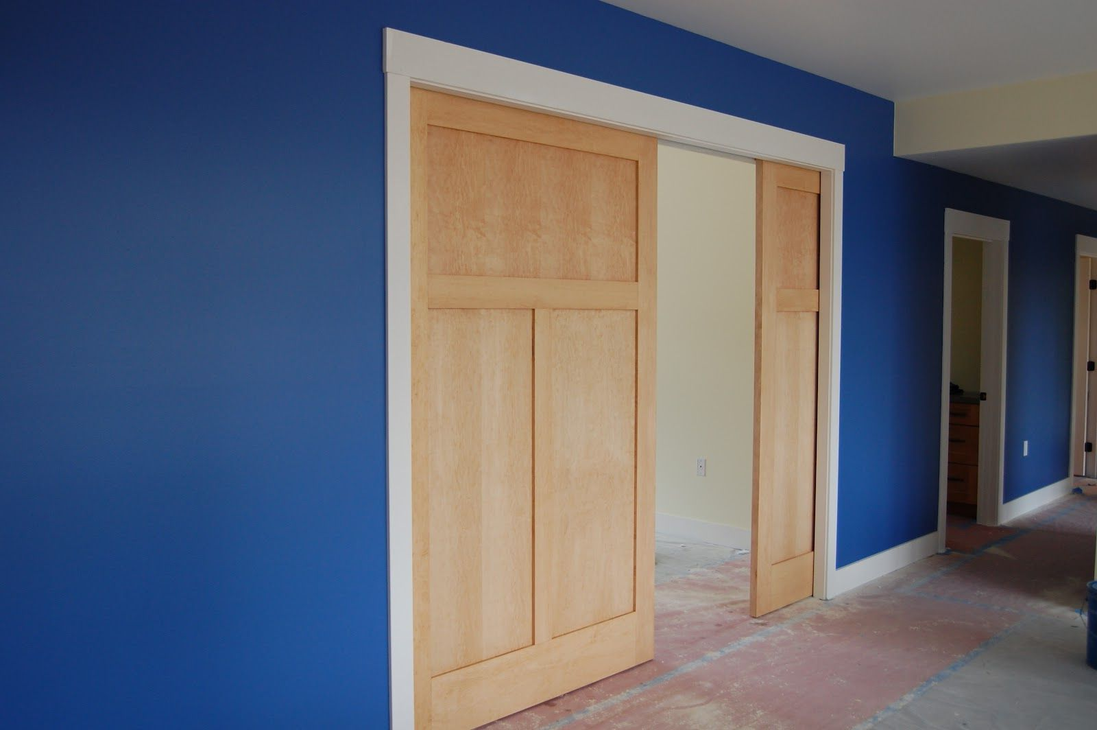 Large wooden pocket interior doors and blue walls in the room