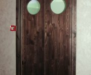 Swing door made of natural wood covered with stain