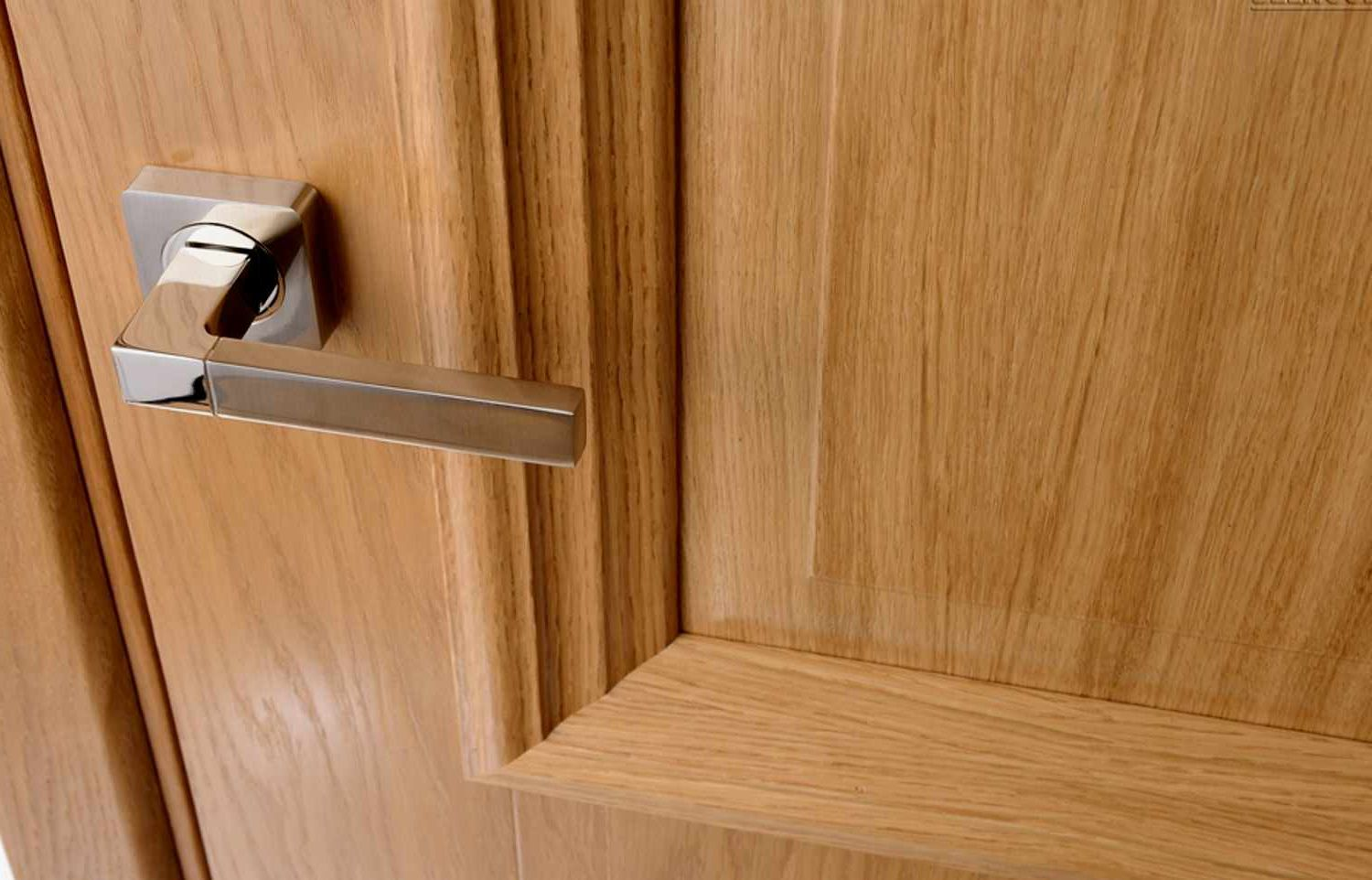 The door covered with wood veneer with a chrome handle