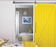 Wooden sliding interior door is painted in yellow color