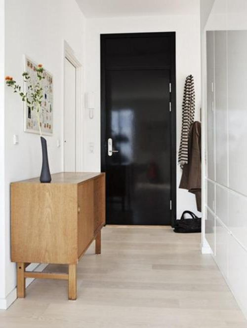 Black interior door with white walls and light floor