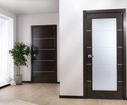 Modern dark door in an apartment with a light floor