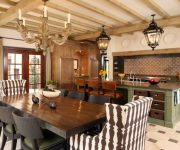 Antique ceiling lamps, wooden table and wicker chairs in the kitchen of an Italian style