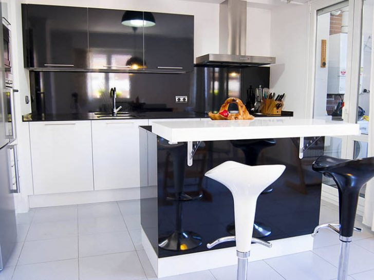 Black with white modern high-tech kitchen with bar chairs and tiled floor