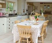 Chairs made of natural wood, table with tablecloth and white wardrobes for kitchen in country style
