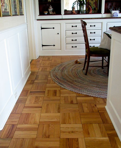 Floor parquet boards and white furniture in the country style kitchen