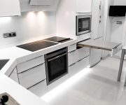 Household appliances in a white kitchen in high-tech style – Microwave, stove, oven, TV