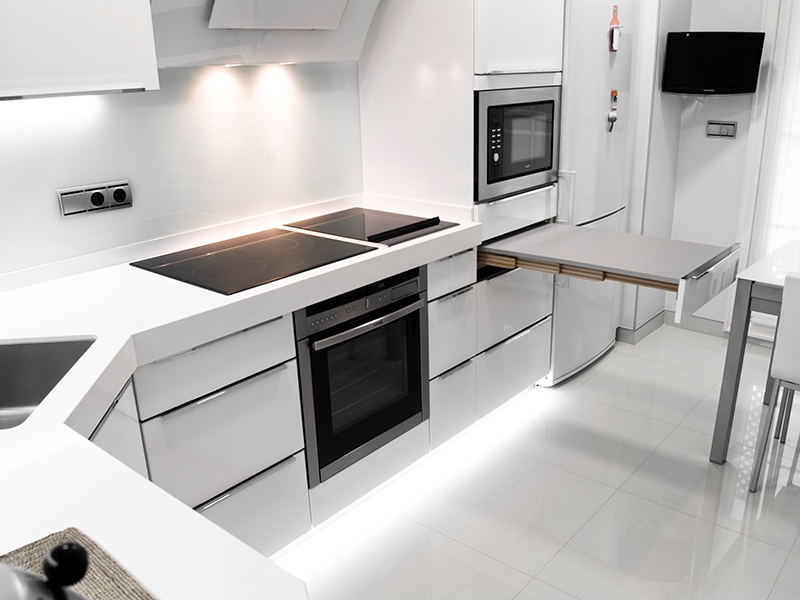 Household appliances in a white kitchen in high-tech style - Microwave, stove, oven, TV