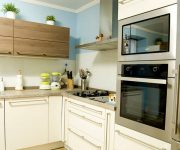 Kitchen High-Tech Style – Wooden facades of light shades soften this strict style